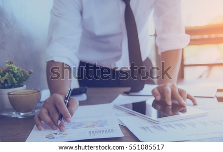 Hands of Businessman working on Laptop Computer with Data Charts #551085517
