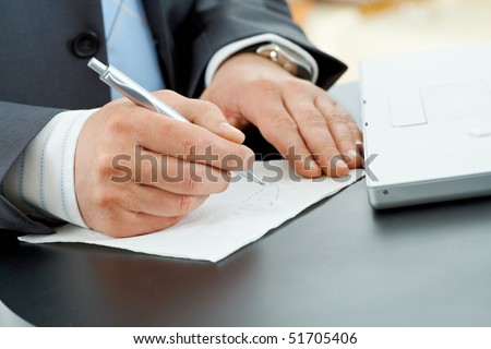 Hands of businessman writing notes on paper napkin with pen.