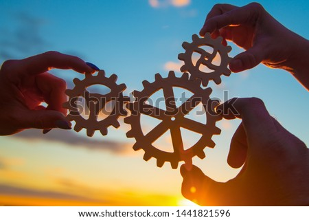 hands of businessmen assemble a puzzle from gears against the sky in the sunset. business concept idea, partnership, innovation, teamwork, cooperation