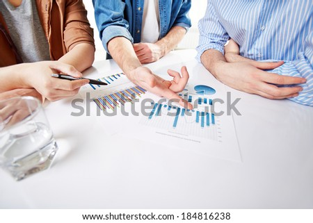 Hands of businessmen during presentation of market analysis