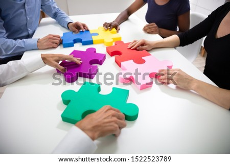 Hands Of Businesspeople Building Colorful Jig Saw Puzzles Together Over White Desk At Workplace
