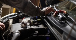 Hands of car mechanic. Protective gloves and tools. Auto service. Car repairing and maintenance.