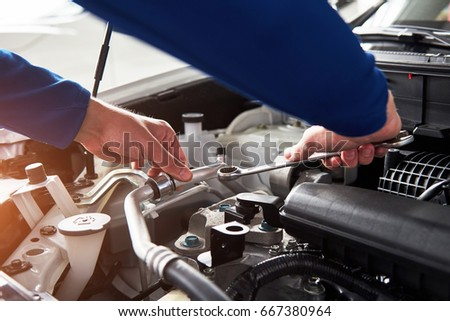Hands of car mechanic with wrench in garage #667380964