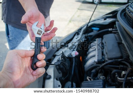 Hands of car mechanic with wrench in garage. The hand of a car mechanic with a wrench in the workshop, Two mechanics sharing metal spanner. #1540988702