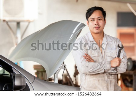 Hands of car mechanic with wrench in service center car #1526482664