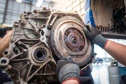 Hands of car mechanic working in auto repair service. Car mechanic fixing flywheel
