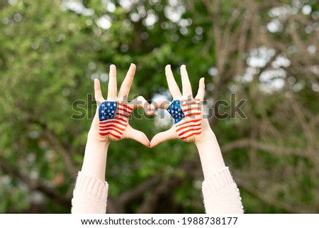 Hands of child painted in American flag color in heart shape. Patriotic holiday. Independence Day, Flag Day, 4th July, 14 June. Little girl show love gesture with hands with USA flag.