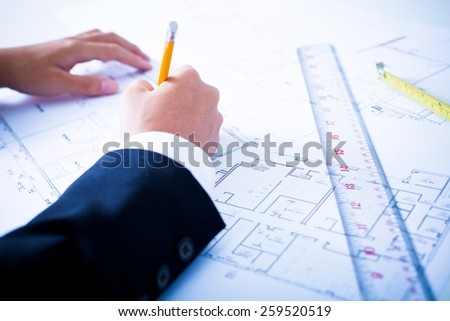 Hands of civil engineer correcting a blueprint