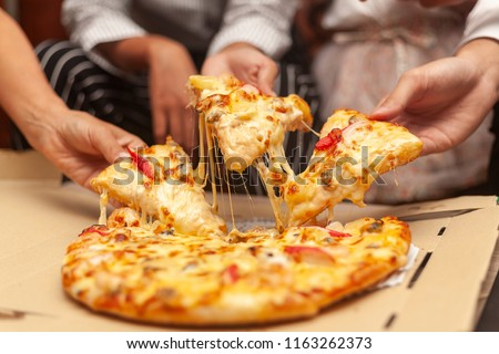 hands of colleague or friends eating pizza After a long meeting at office. They are having party at home, eating pizza and having fun. leisure, food and drinks, people and holidays concept