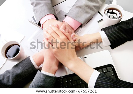 Hands of companions making pile at workplace