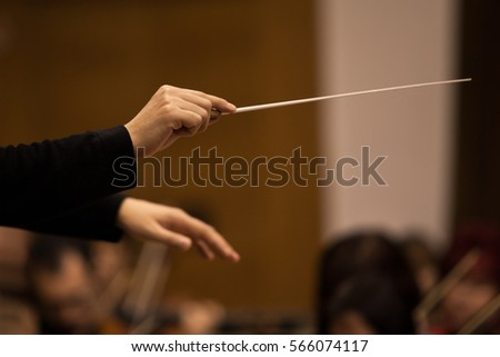 Hands of conductor close up in dark colors #566074117