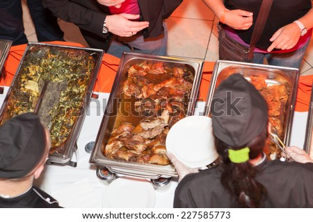 Hands of cook serving food at a catered event
