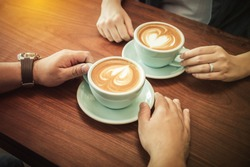 hands of couple drinking coffee at cafe together ,heart shape latte art in coffee cup.