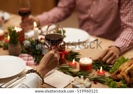 Hands of couple drinking red wine at Christmas table