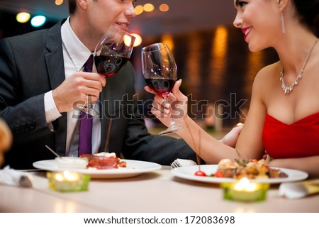 hands of couple toasting their wine glasses over a restaurant table during a romantic dinner