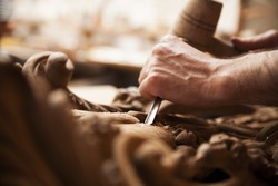 Hands of craftsman carve  with a gouge in the hands on the workbench in carpentry