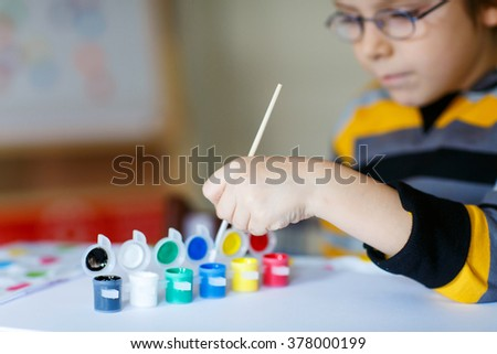 48318243473 Hands of cute happy preschool kid boy with glasses at home making homework. Little  child