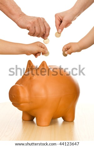 Hands of different generations putting coins in piggy bank - saving money concept