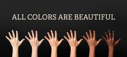 Hands of different people and text ALL COLORS ARE BEAUTIFUL on dark background. Stop racism