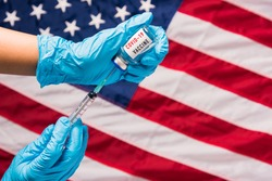 Hands of doctor wear gloves holding coronavirus (COVID-19) vial vaccine and syringe on flag United States of America background, USA Vaccination