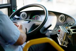 Hands of driver in a modern bus by driving.Concept - close-up of bus driver steering wheel and driving passenger bus