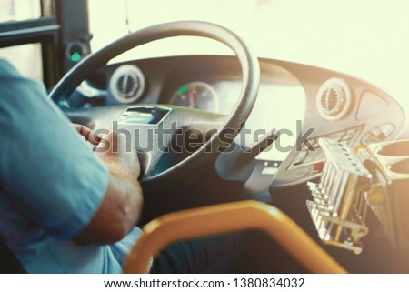 Hands of driver in a modern bus by driving. Concept of bus driver steering wheel and driving passenger bus. Toning. #1380834032