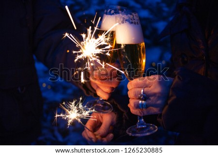 hands of elderly couple holding sparkles and glasses of champagne celebrating New Year #1265230885
