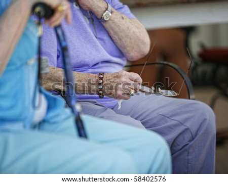 Hands of elderly woman holding glasses