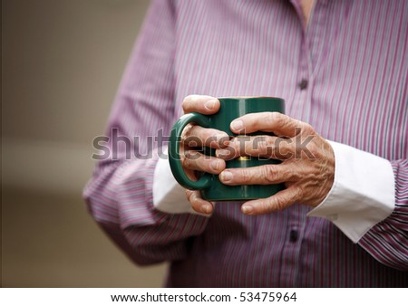 Hands of elderly woman with arthritis holding cup