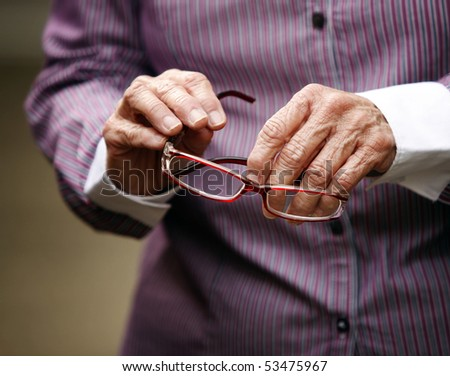 Hands of elderly woman with arthritis holding glasses