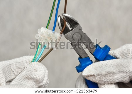 hands of electrician cutting wires with clippers