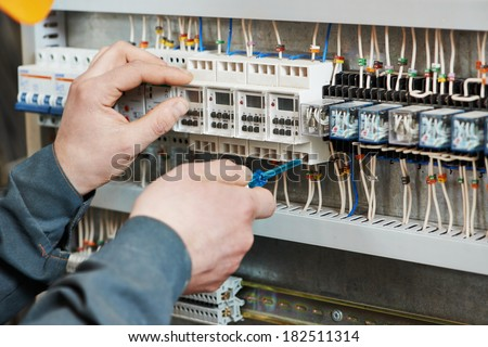 Hands of electrician with screwdriver tighten up switching electric actuator equipment in fuse box stock photo