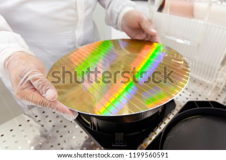 Hands of engineer holding a silicon wafers with reflection light and workers in white suits working at clean room laboratory semiconductor production.blurred background