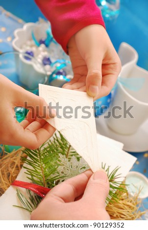 hands of family members sharing with traditional christmas eve wafer above the  festive table