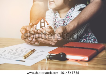 Hands of family together holding house after signing contract document for buy house. first time home buyers, real estate purchase concept.