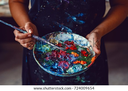 Hands of female artist holding messy dirty palette  with different paints and paintbrush in art studio. Lifestyle and hobby concept