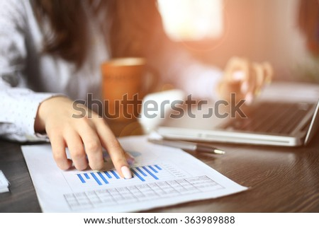 Hands of financial manager taking notes when working