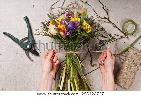 Stock Photo hands of florist making bouquet spring flowers