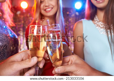 Hands of friends cheering up with champagne at party