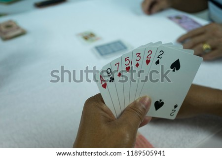 Hands of gambler playing card in rummy game. Close up card in hand. #1189505941