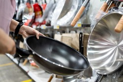 Hands of girl holding a new pan,choosing black teflon frying pan,asian  customer deciding to buy non-stick frying pan for cooking food in her kitchen,shopping cookware household goods at supermarket