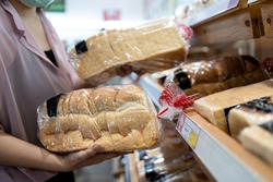 Hands of girl holding sliced white bread product,choosing wheat bread in plastic bag packaged,fresh homemade baked bread in the bakery shop while shopping food,woman buying or selecting food quality