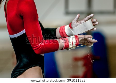 hands of girl in gymnast grips before performing on horizontal bar