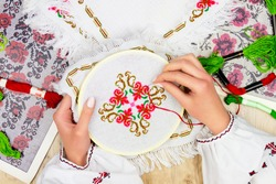 Hands of girl / woman / female in ukrainian traditional shirt sewing embroidery pattern in embroidery frame. Embroidery schemes and colorful threads on background.