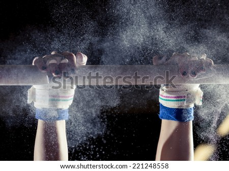 hands of gymnast with chalk on uneven bars