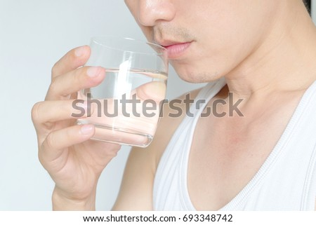 Hands of handsome men holding glass of water are drinking pure water. Health concept - Shutterstock ID 693348742