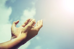Hands of human are pray and worship on blue sky background with sunlight, Soul of prayer man, Spirituality with believe and religion