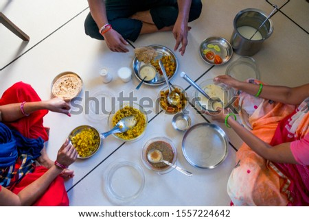 hands of indian men and women having traditional gujarati thali  lunch on floor for being of low caste #1557224642