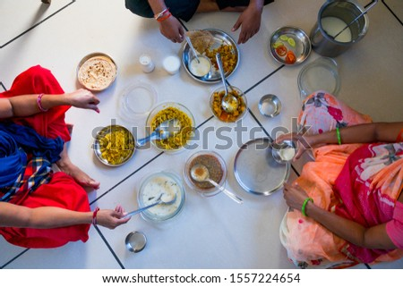 hands of indian men and women having traditional gujarati thali  lunch on floor for being of low caste #1557224654