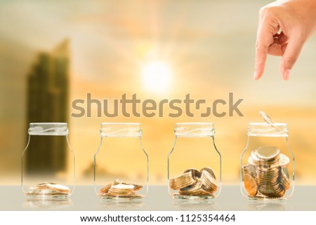 Hands of investors with saves a coin in the bottle bank with growing on photo blur cityscape on sunlight background, Business investment and saving money concept. #1125354464
